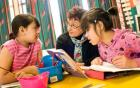 A teacher and two students reading and discussion a book