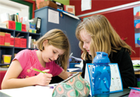 Two primary age school children in a classroom setting, working together on a written exercise