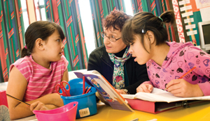 An adult educator works on a reading exercise with two primary age children