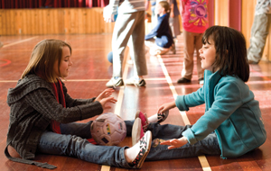 Two primary age children are sitting in a gymnasium floor, rolling a ball between them